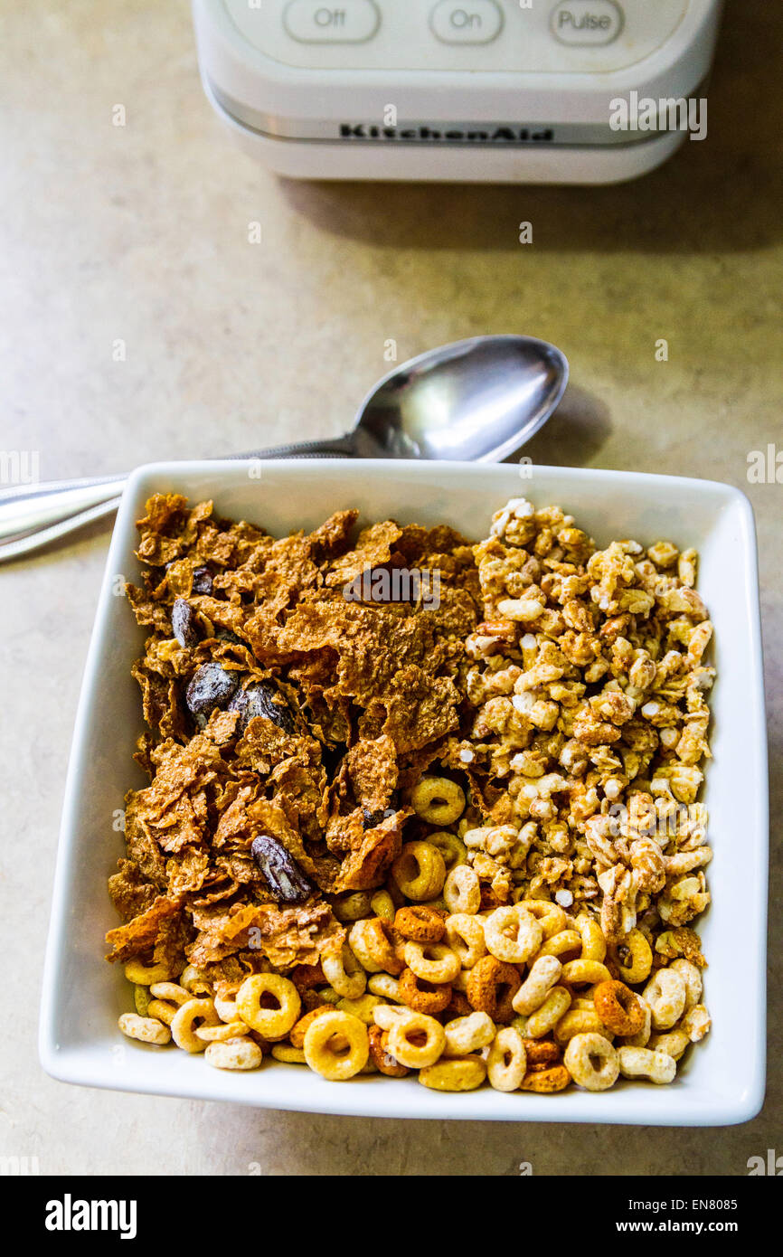 Cheerio's, Kashi Go Lean Crunch, and store brand raisin bran cereals in a square bowl for breakfast. - Stock Image