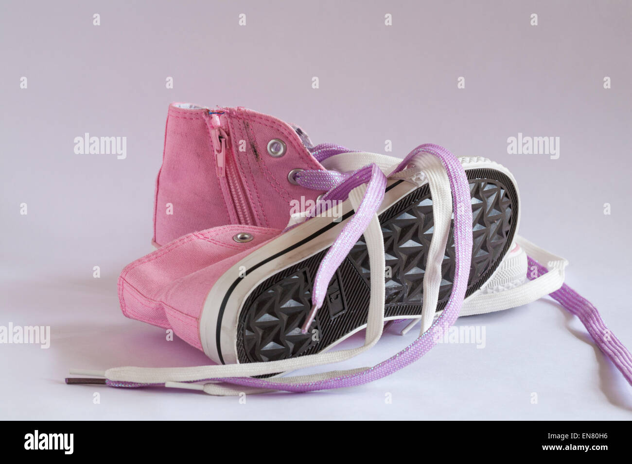 Pair of pink canvas tie up shoes isolated on white background - Stock Image