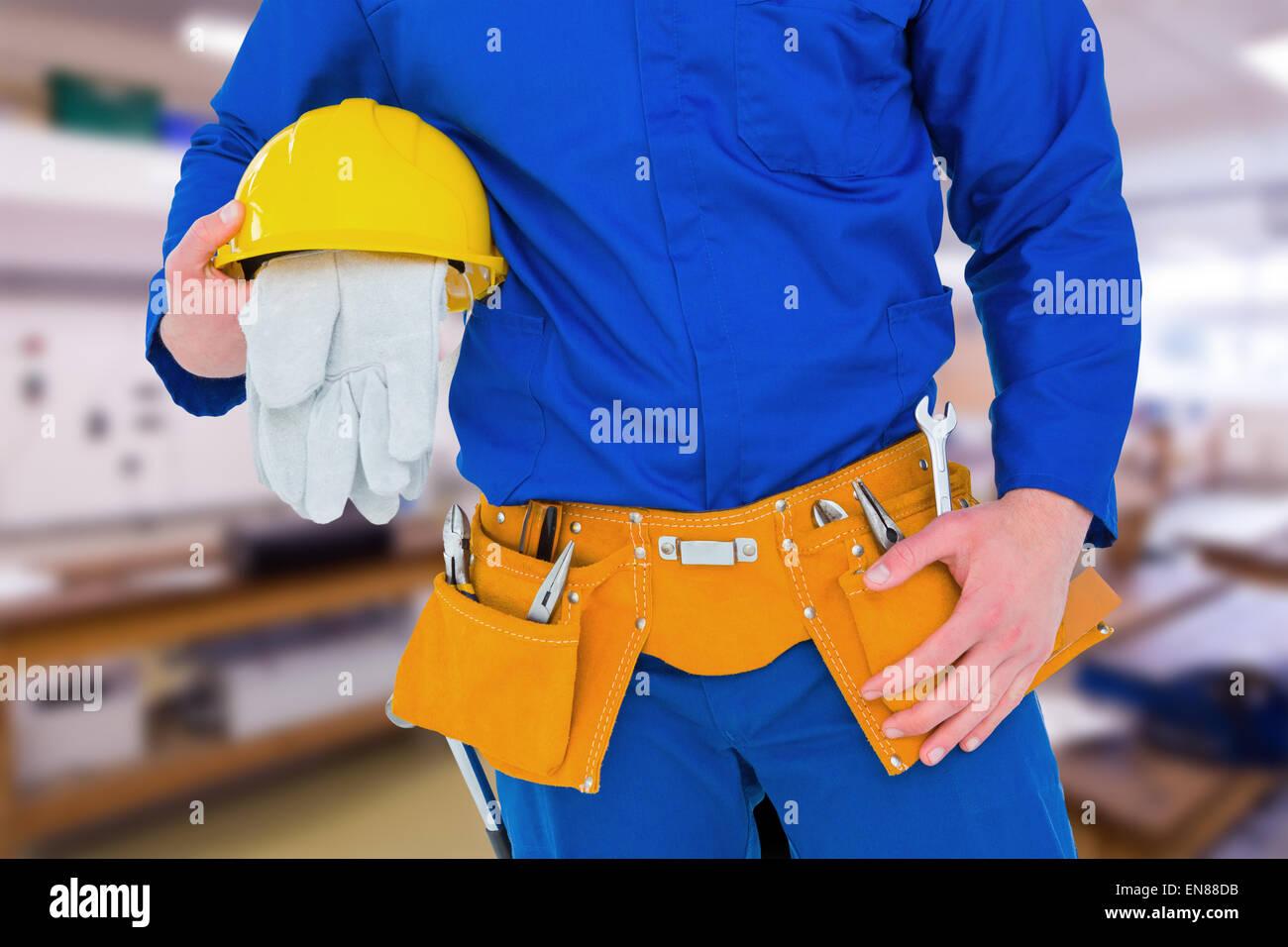 Composite image of handyman holding helmet - Stock Image