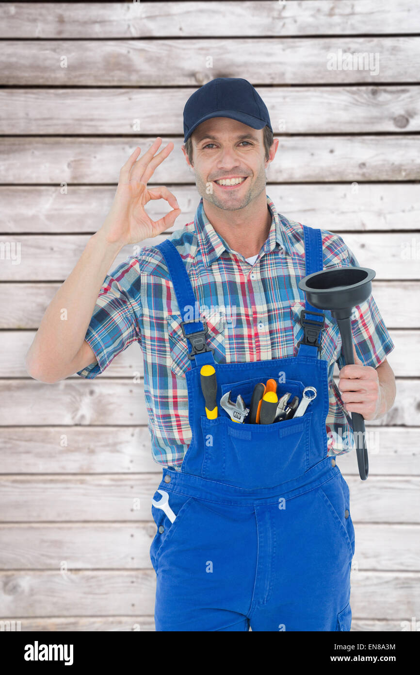 Composite image of plumber holding plunger while gesturing ok sign - Stock Image