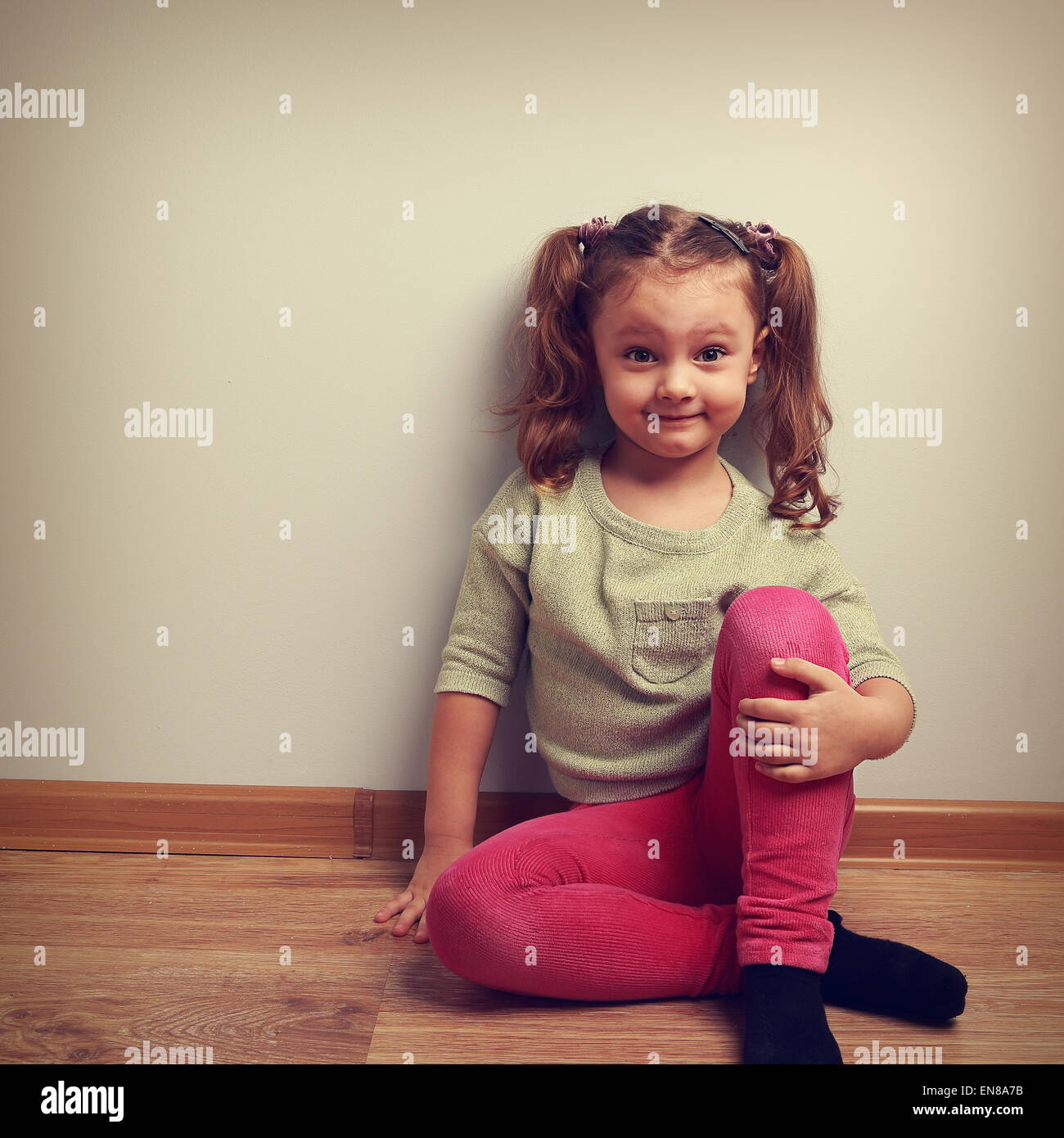 Grimacing fashion girl sitting on the floor and smiling. Vintage closeup portrait - Stock Image