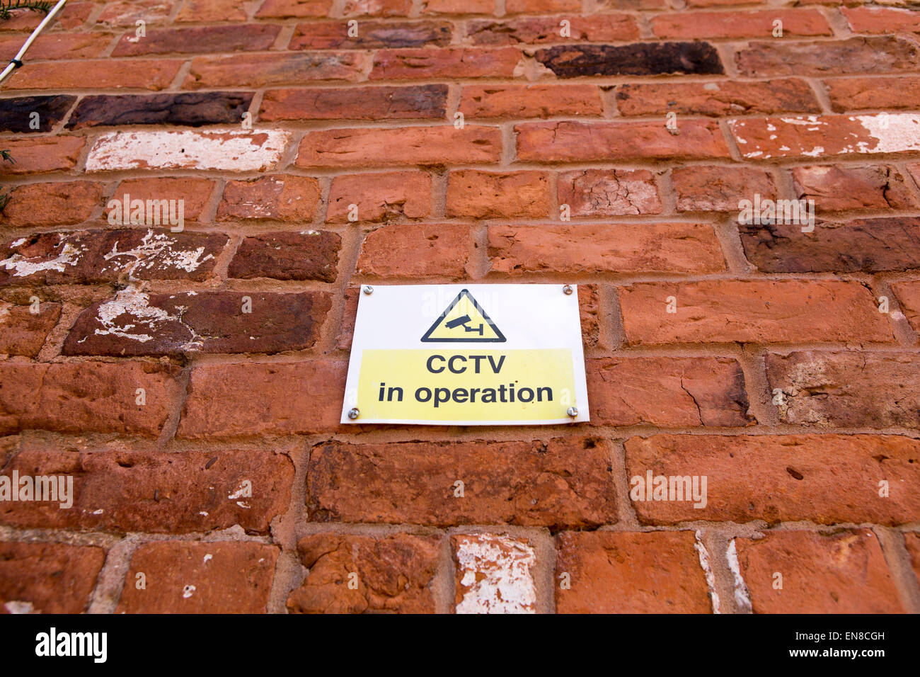 CCTV in operation sign on a red brick wall - Stock Image