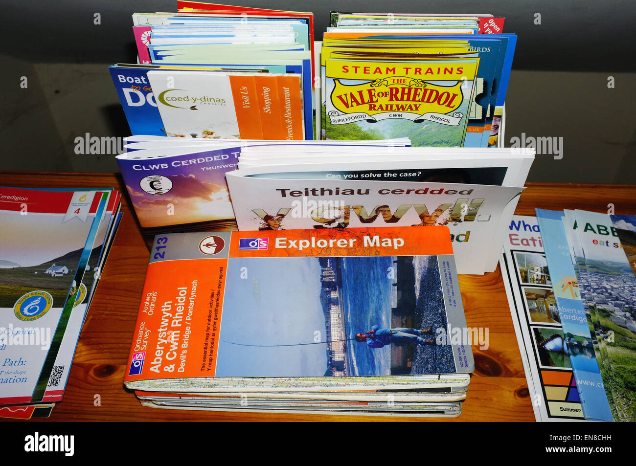 A collection of maps and tourism leaflets on display inside a B&B in Mid Wales. - Stock Image