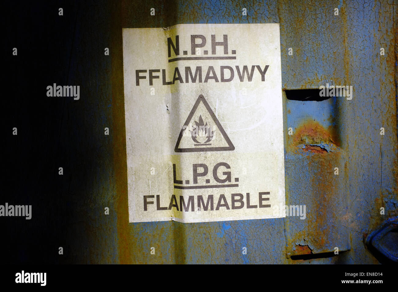 A bilingual highly flammable warning sign in English and Welsh on the side of a container. - Stock Image