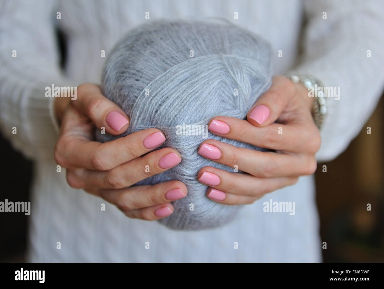 Skein of gray thread in female hands - Stock Image