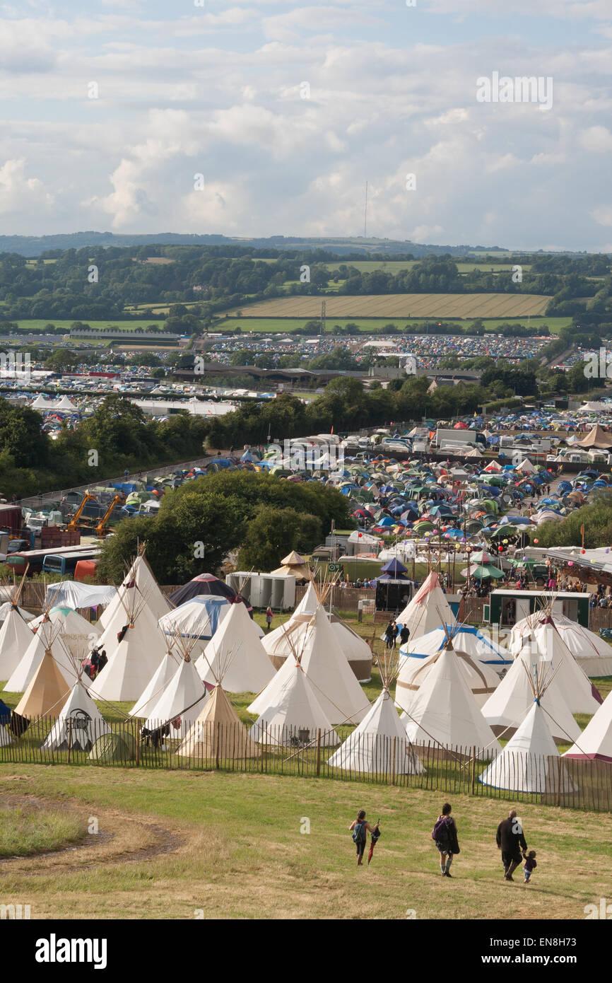 GLASTONBURY, UK - JUNE 28: Family walk towards tipi tents at Glastonbury Festival on 28th June, 2014 at Pilton Farm, - Stock Image