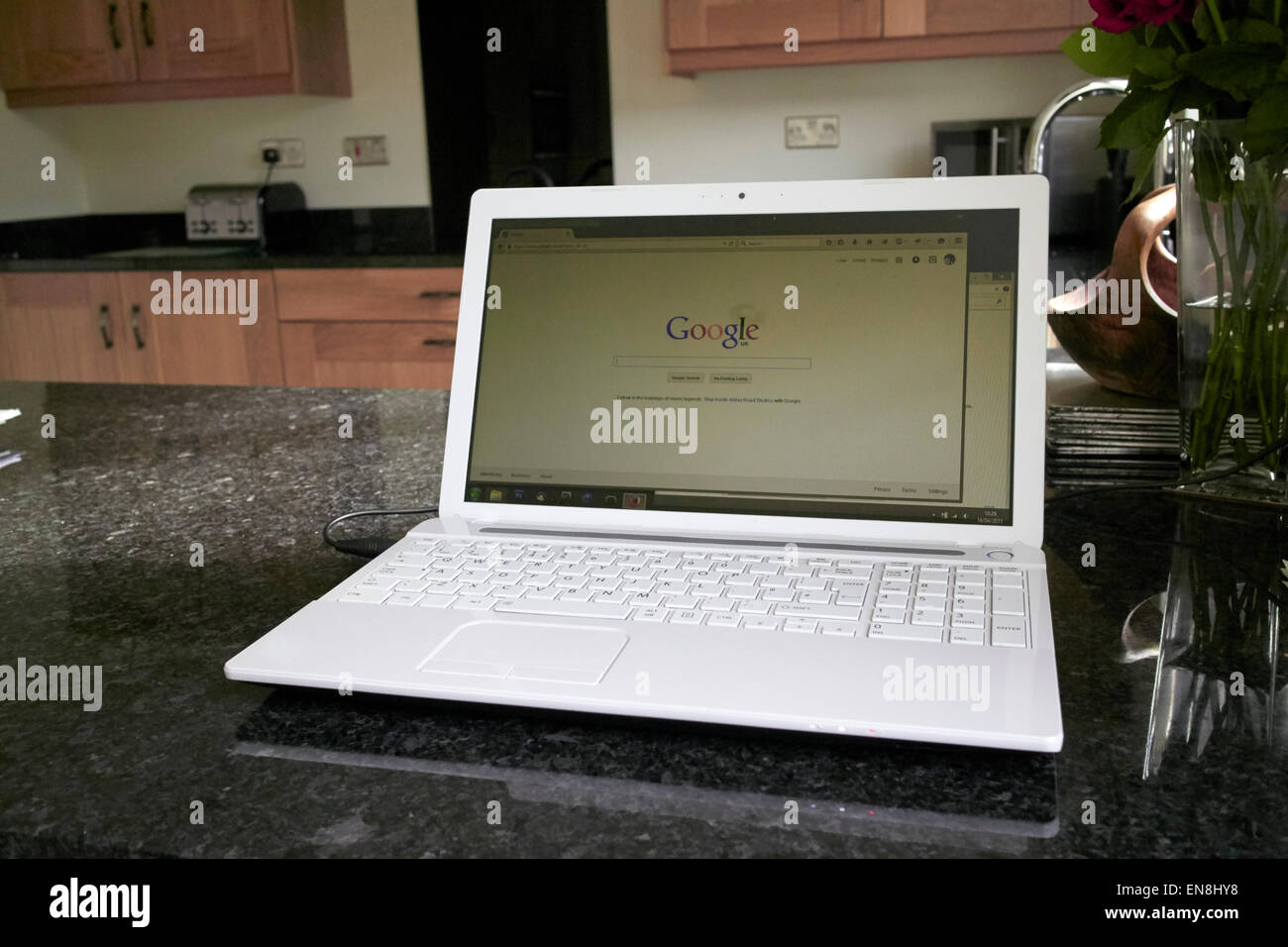 laptop in the kitchen with google search screen working from home in the uk - Stock Image