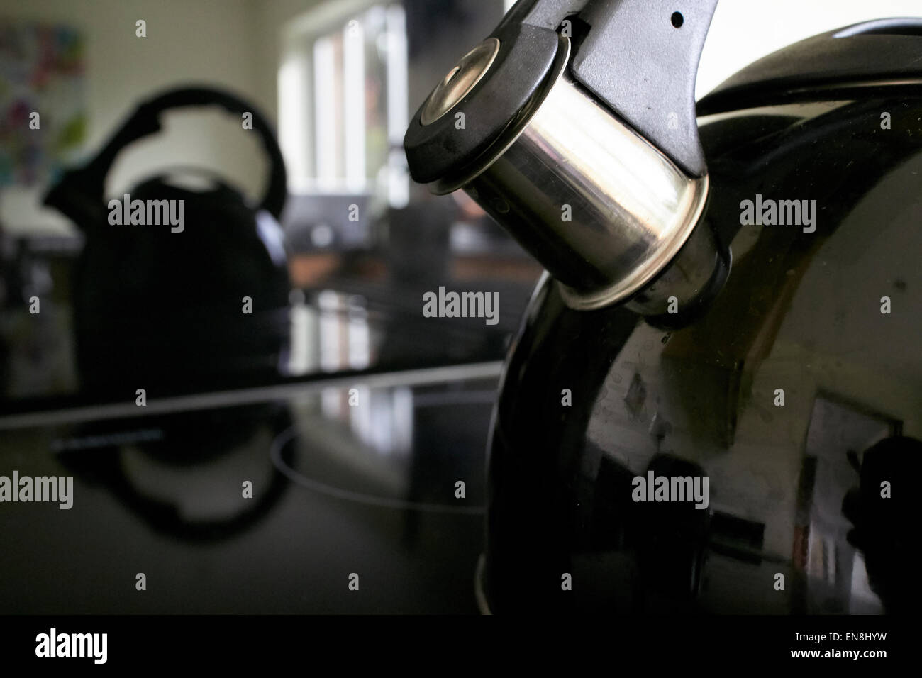 spout of whistling kettle on a induction hob in a modern new kitchen - Stock Image