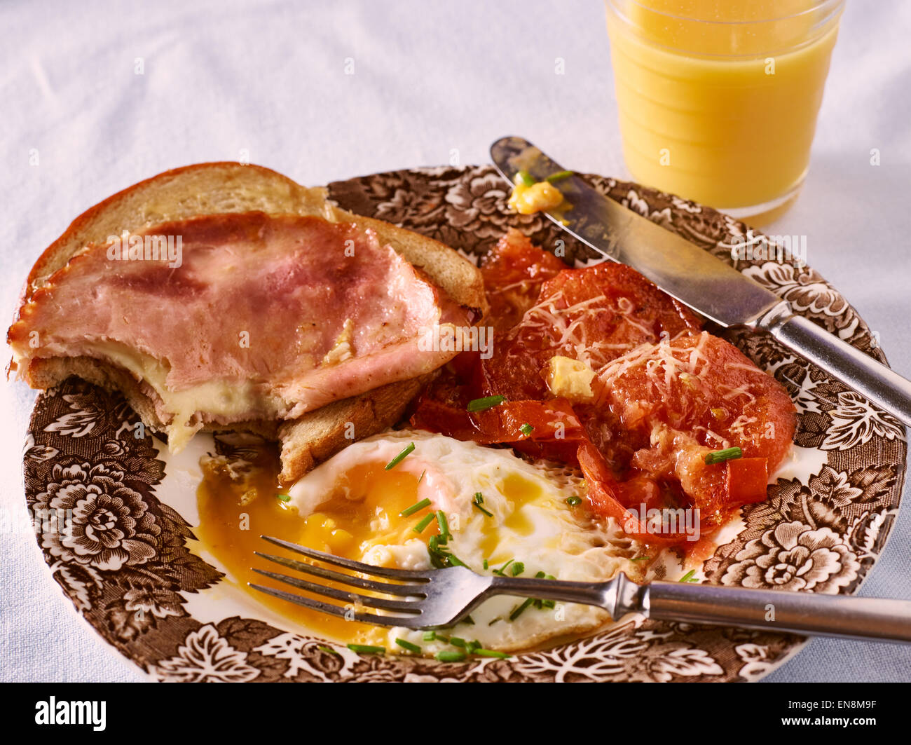 Breakfast, fried egg, tomatoes and bread with a ham Stock Photo