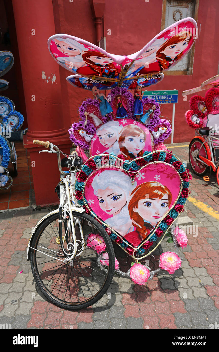 Decorated kitsch cycle trishaw rickshaw with soft toys in Malacca, Malaysia - Stock Image