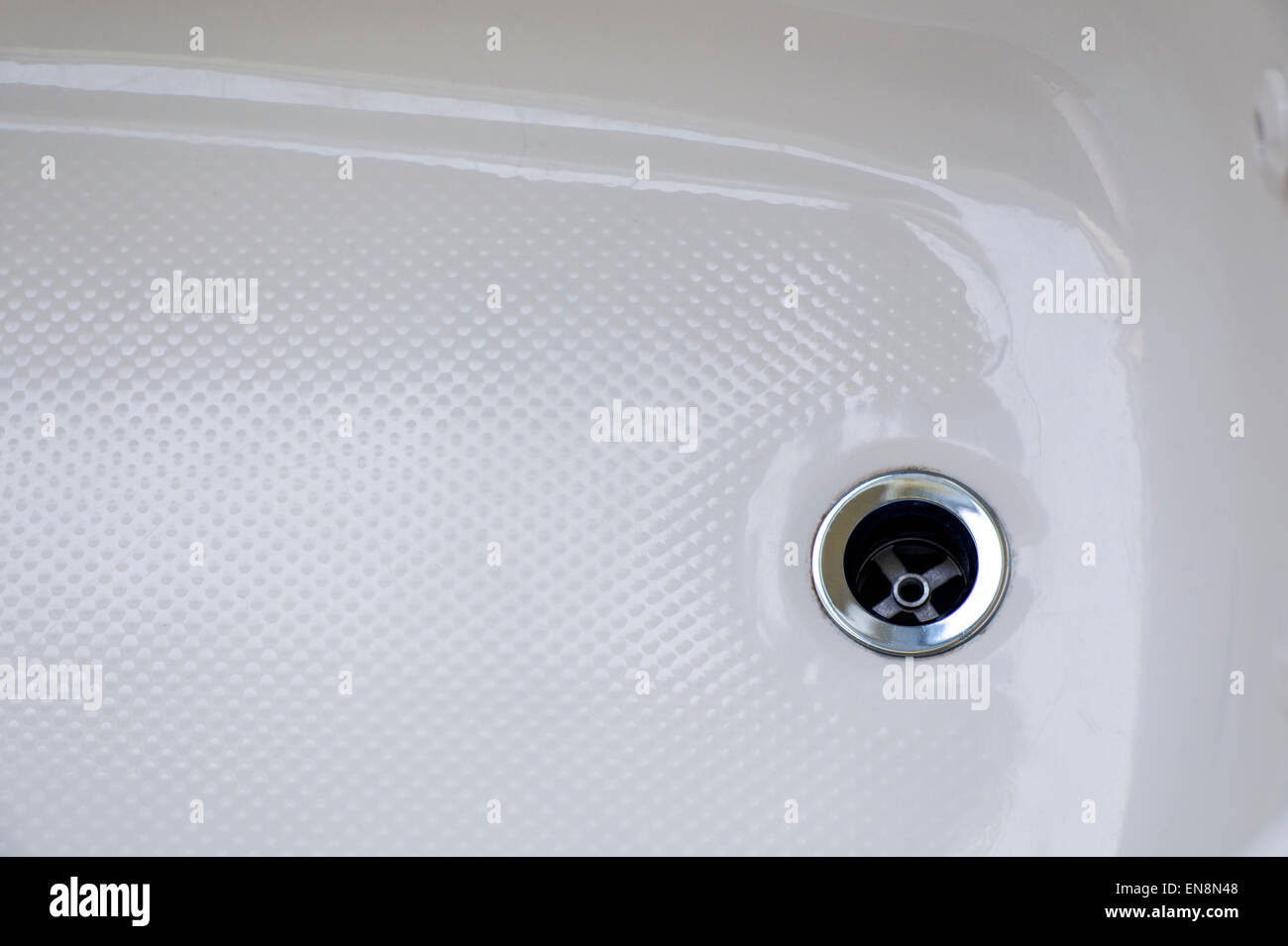 Close up of the drain in a ceramic bath tub - Stock Image