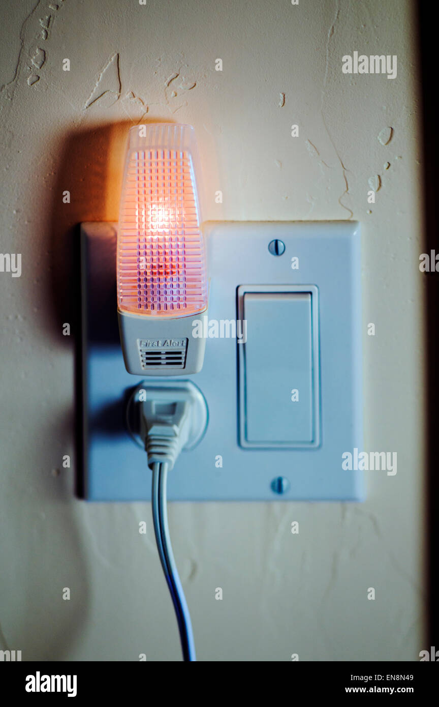 Close up of a night light and electrical outlet in a suburban home - Stock Image
