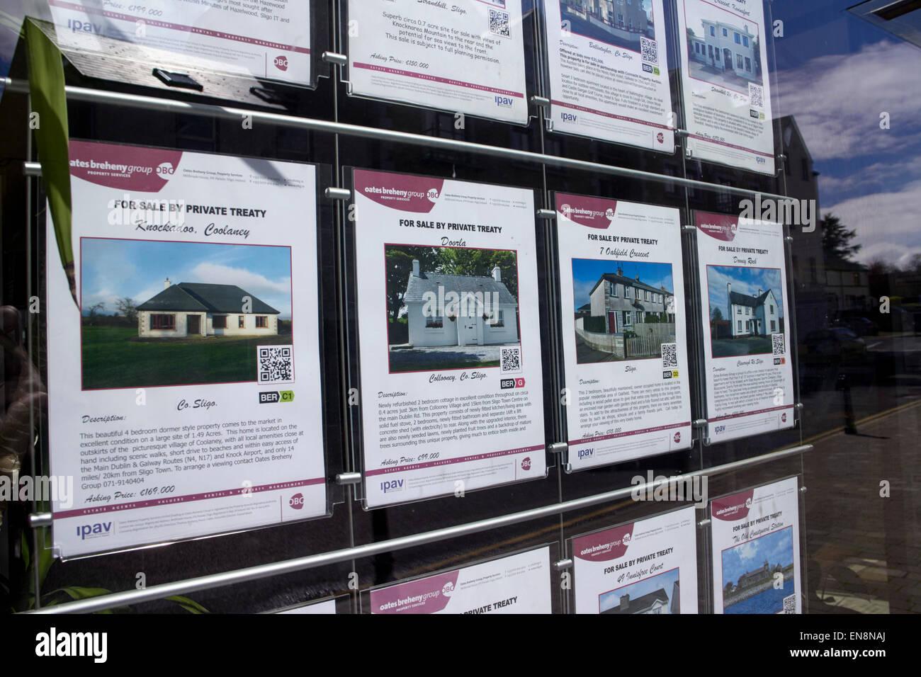properties for sale in an estate agents window sligo republic of ireland - Stock Image
