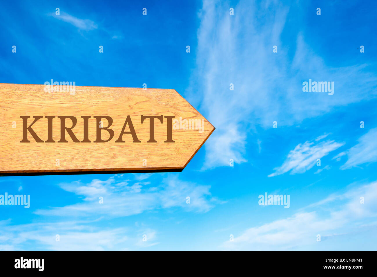 Wooden arrow sign pointing destination KIRIBATI against clear blue sky with copy space available. Travel destination - Stock Image