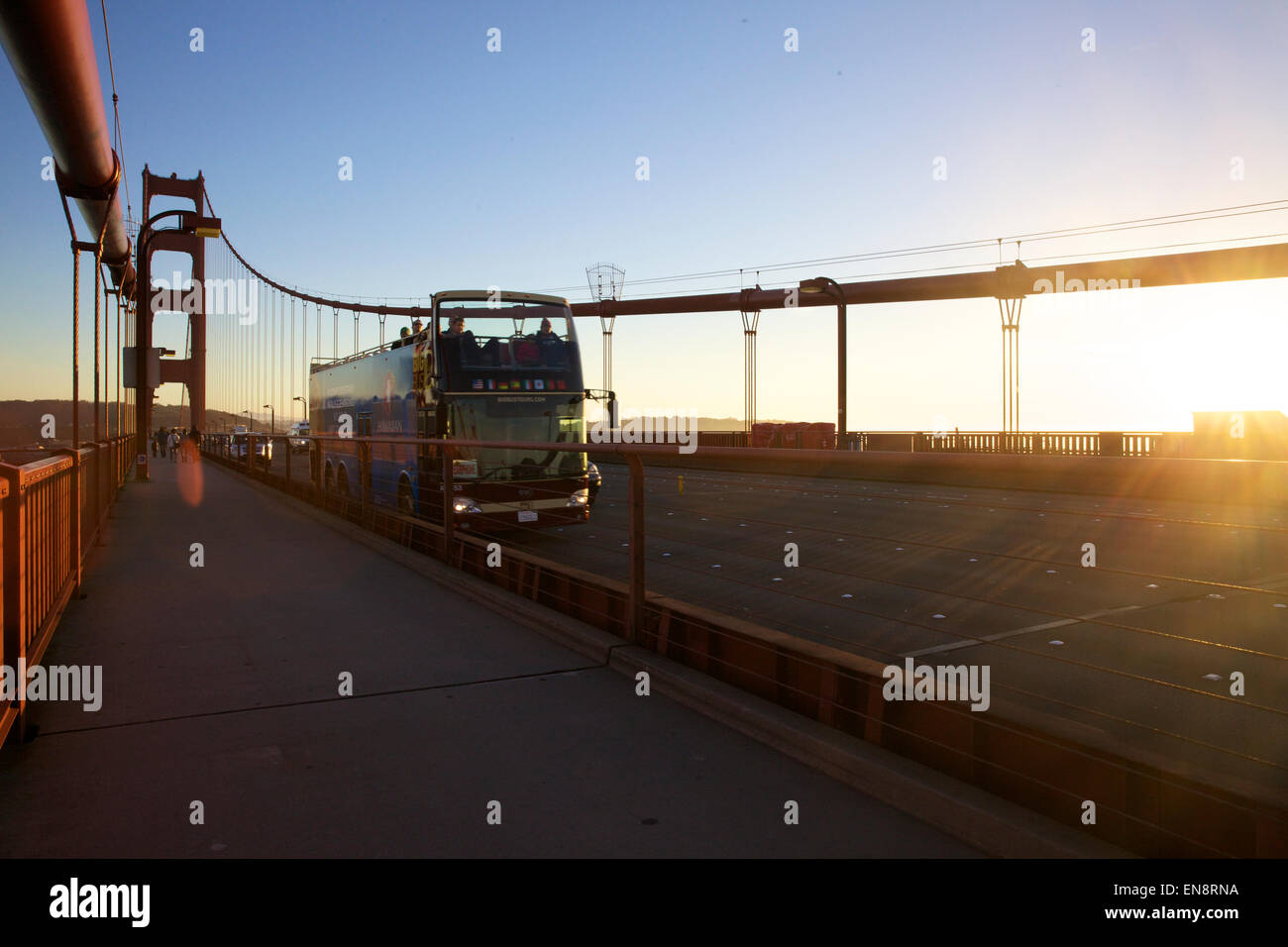 A double decker tourist bus crosses over the Golden Gate Bridge in San Francisco California at sunset. - Stock Image