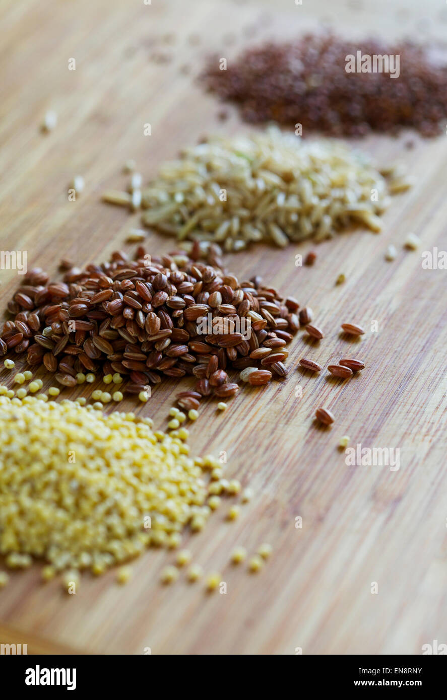 Four piles of uncooked whole grains including millet, red rice, brown rice and red quinoa. - Stock Image