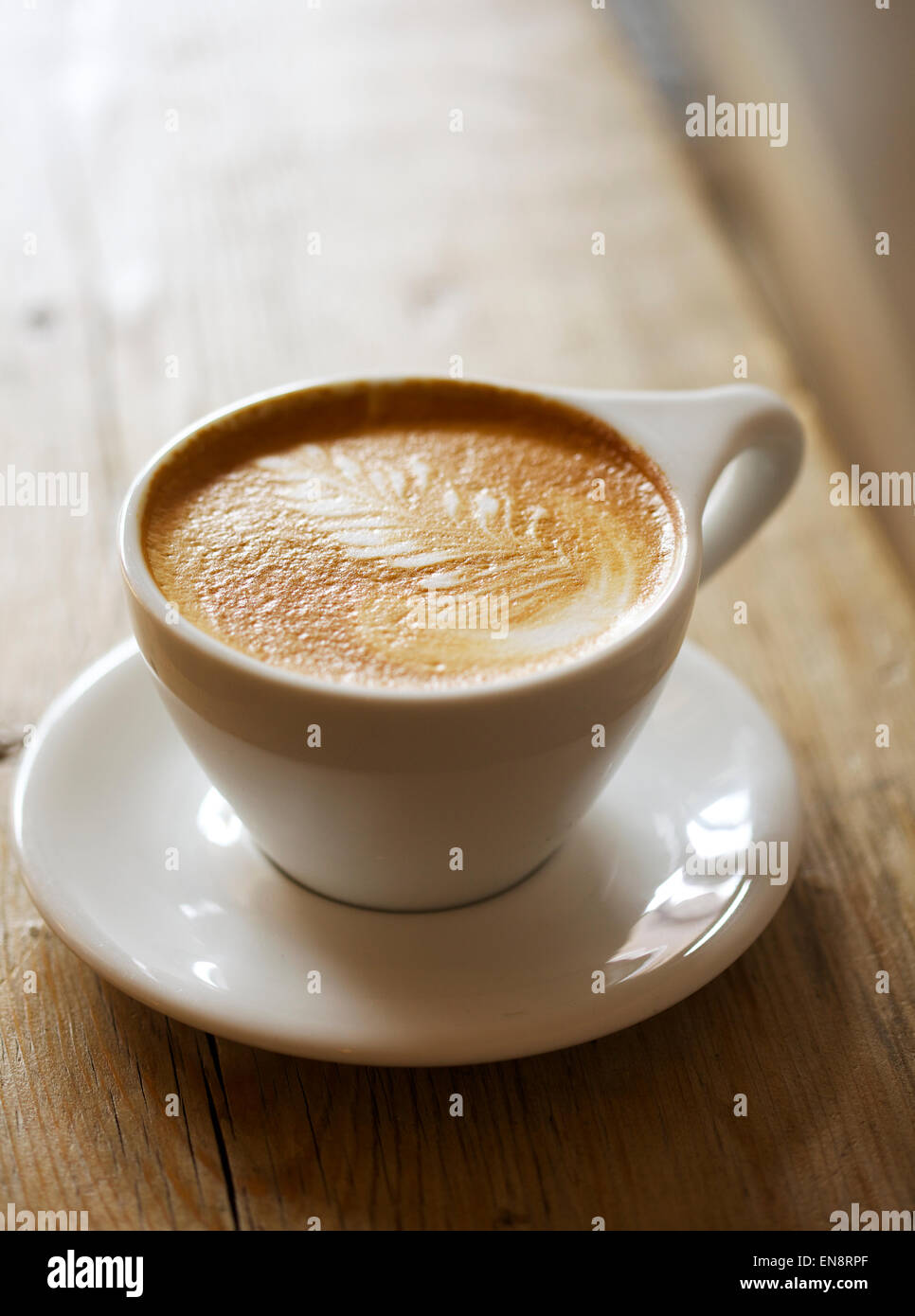 A cappuccino with a leaf pattern in the foam in a white cup with a saucer sitting on a wooden table, background - Stock Image