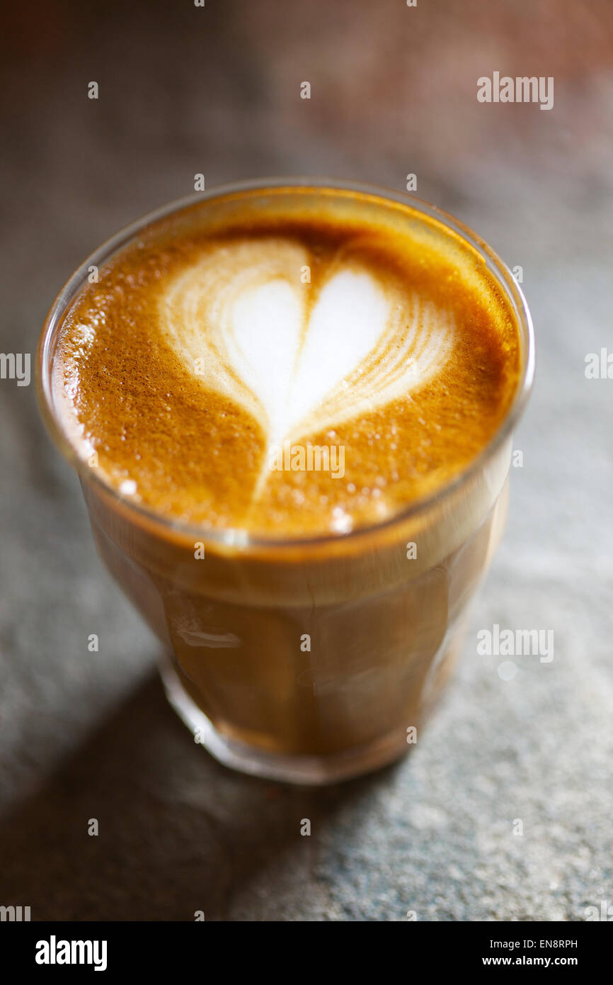 A Cortado with a heart in the foam sitting on a stone surface. - Stock Image