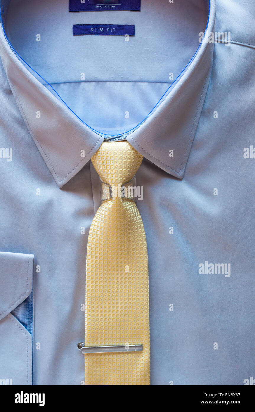 Blue cotton shirt and yellow tie with clip close up Stock Photo