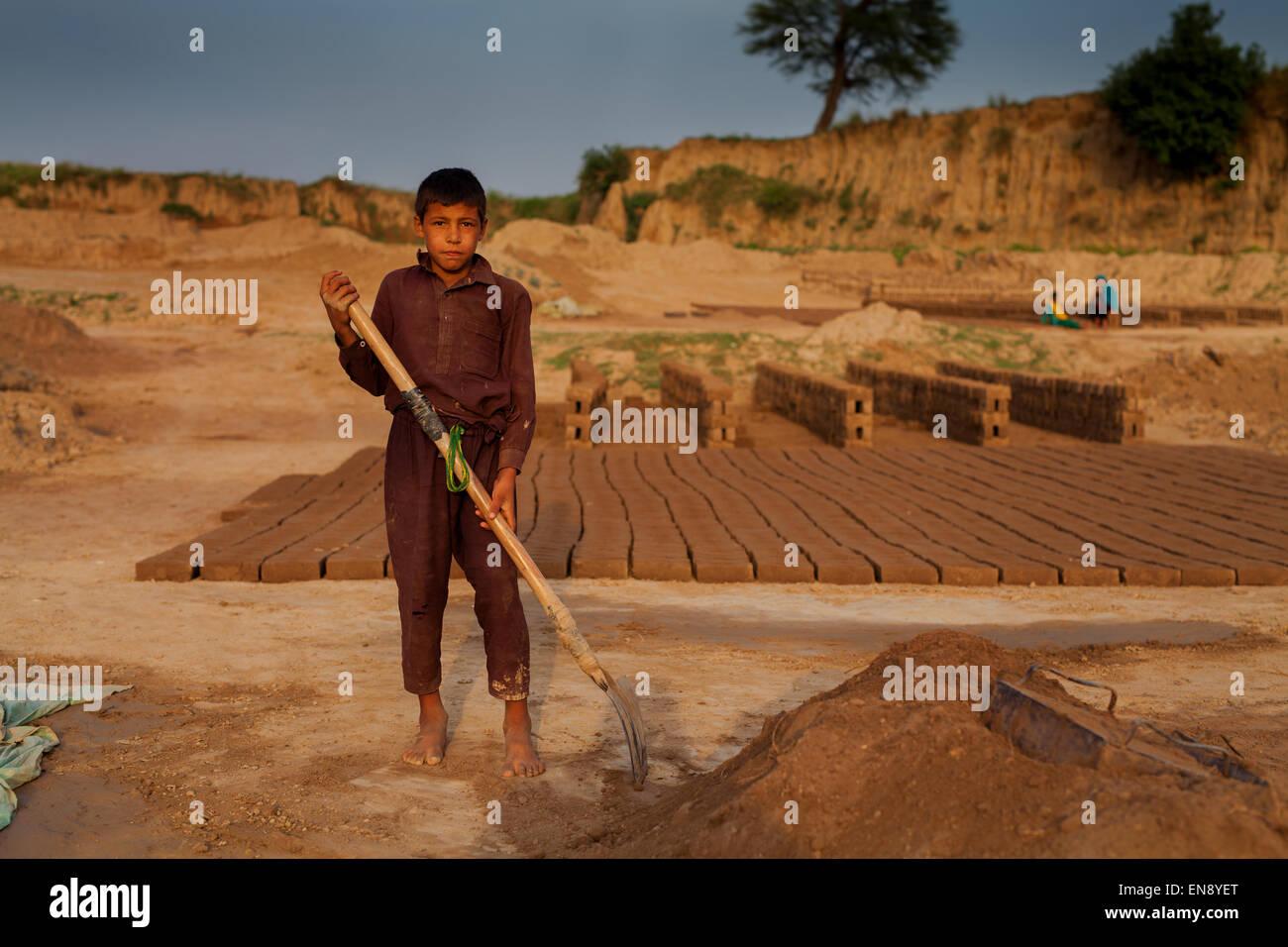 A Child laborer holding a shovel at brick making facility - Stock Image