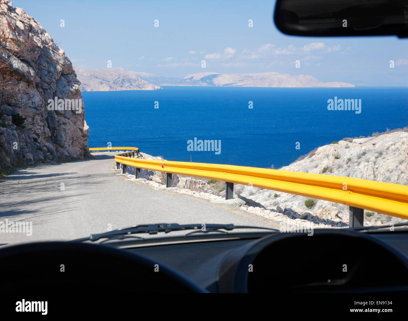 View to Croatian coast, road and blue sea trough the car windshield. - Stock Image