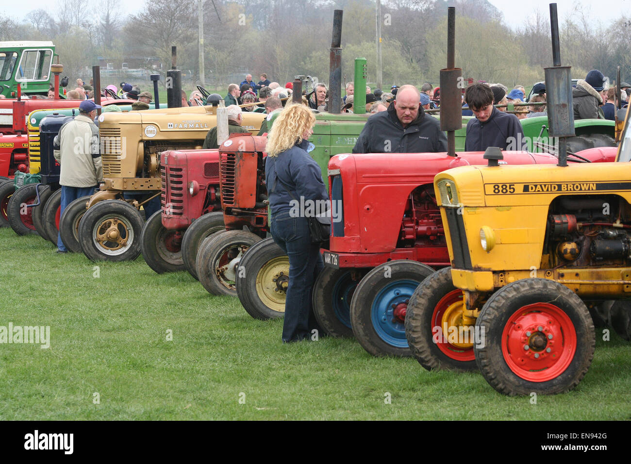 Prospective buyers examine a line of old farm tractors for sale at a ...