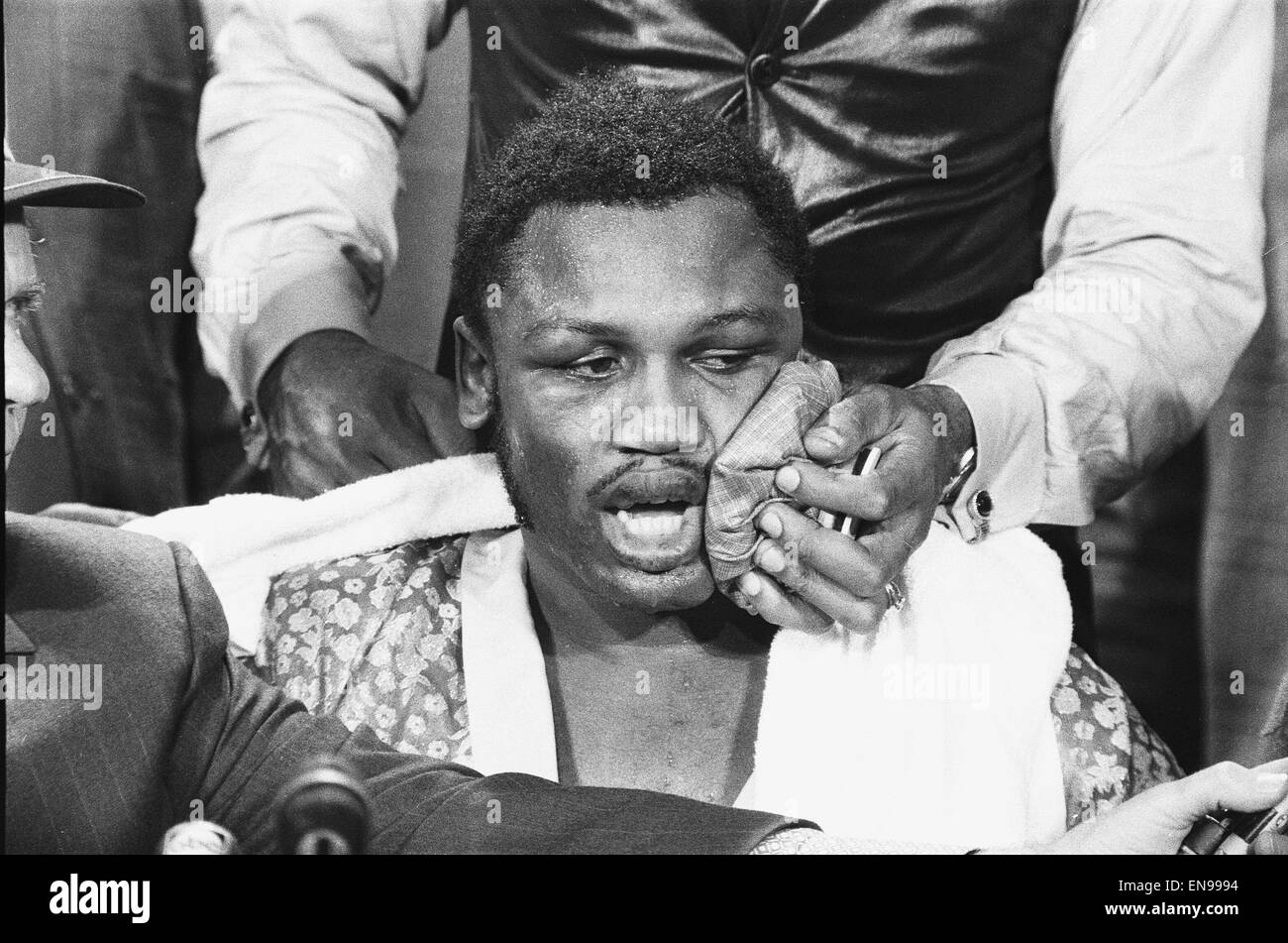 Joe Frazier seen here giving a press conference whilst an aide applies a ice bag to his face to reduce the swelling - Stock Image