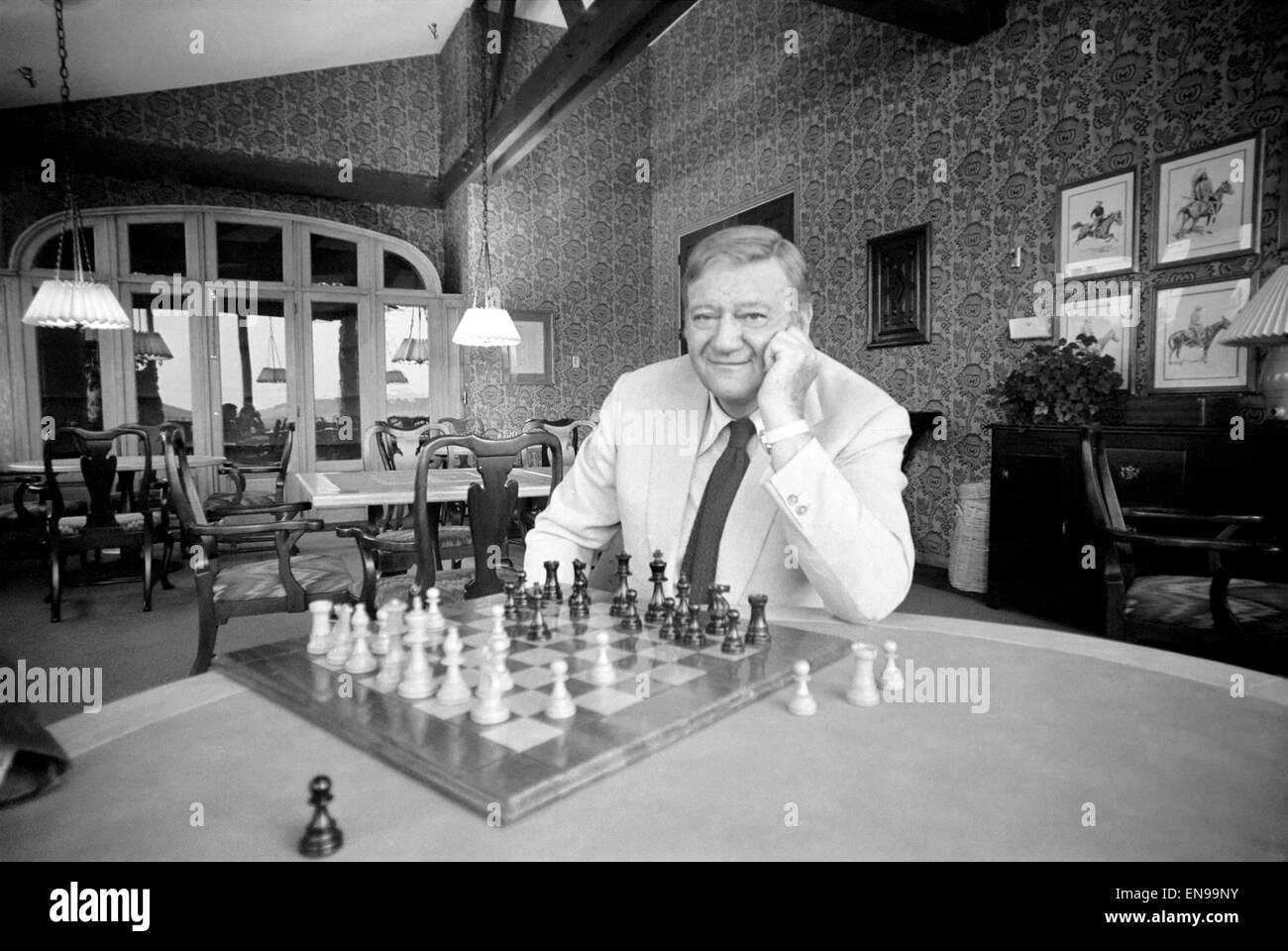 John Wayne who recently starred in 'Brannigan' at home in Texas playing a game of chess. 8th June 1975 - Stock Image