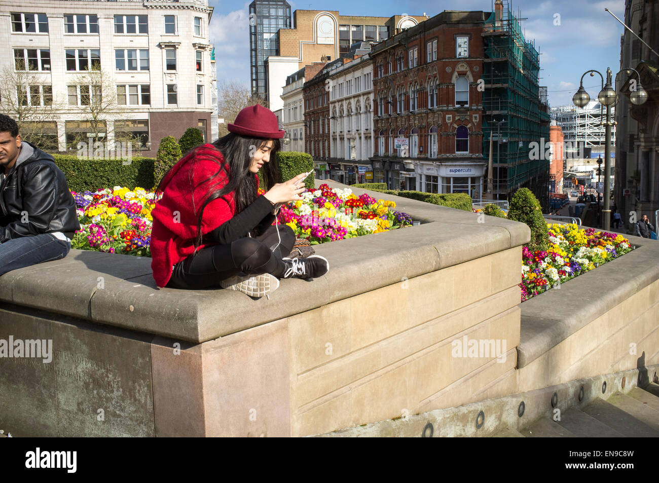 Young Asian woman/girl absorbed using a smart phone and oblivious to city life - Stock Image