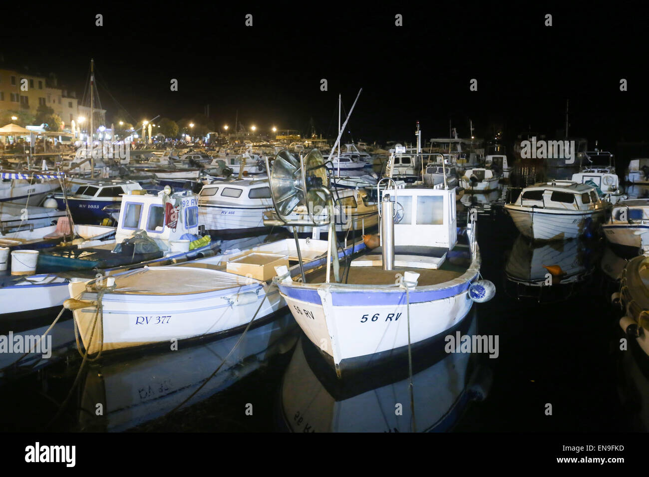A large group of boats anchored in the marina with a view of the city seafront at night in Rovinj, Croatia. - Stock Image