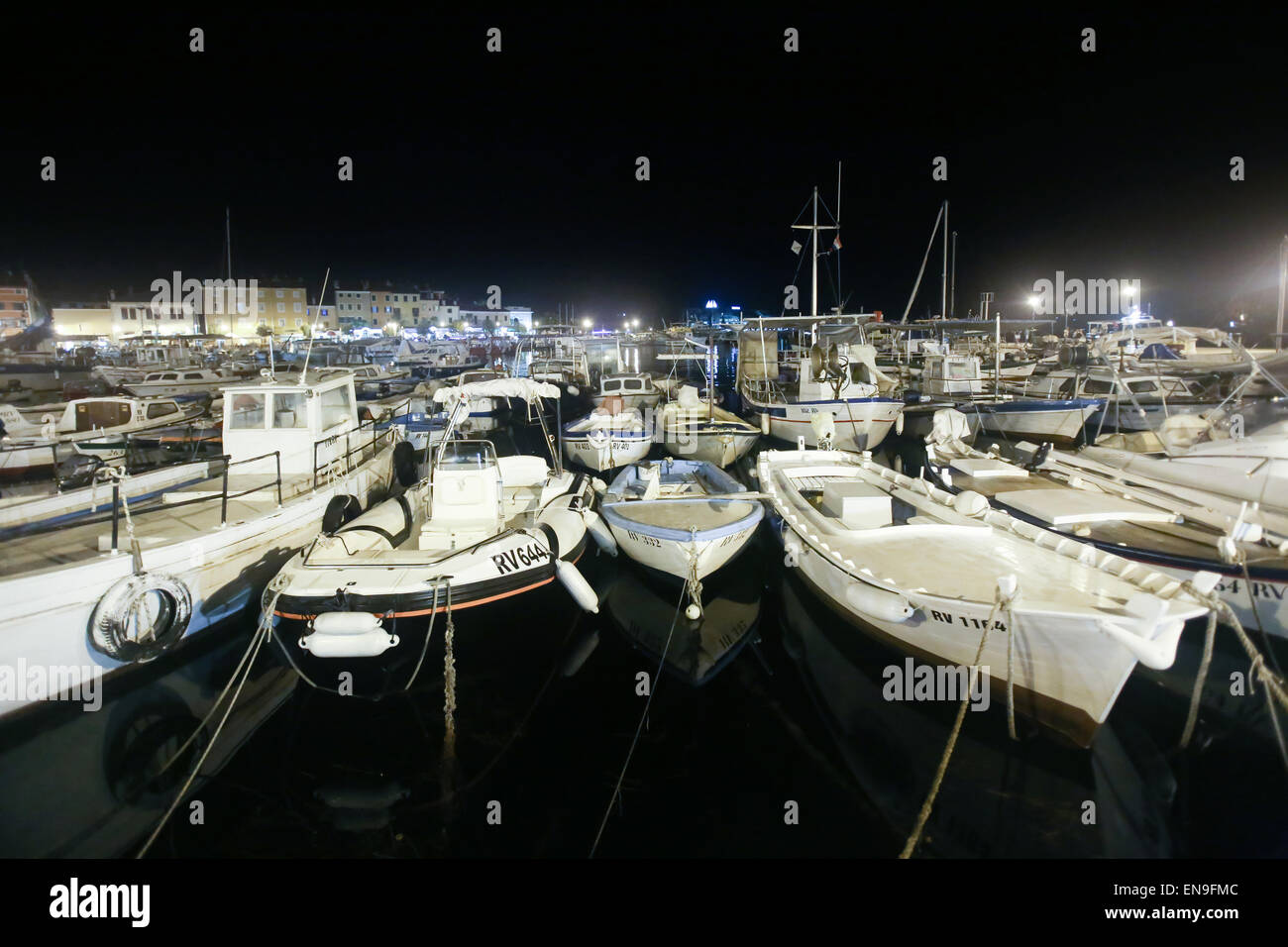 A large group of boats anchored in the marina with a view of the city seafront at night in Rovinj, Croatia - Stock Image