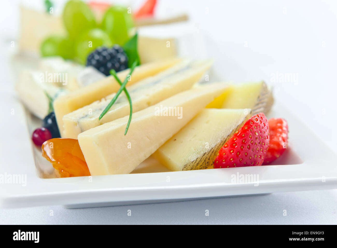 cheese with berries on a white plate Stock Photo