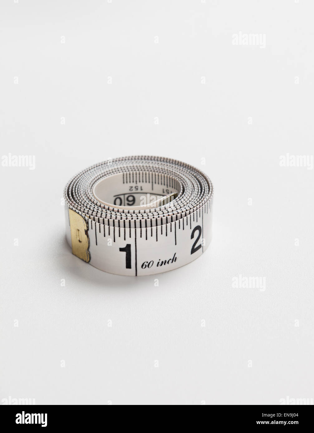 A tape measure on a white background - Stock Image