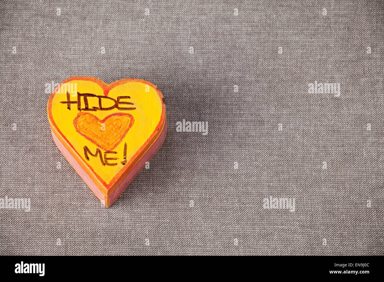 A heart-shaped trinket box with Hide Me written on the top - Stock Image
