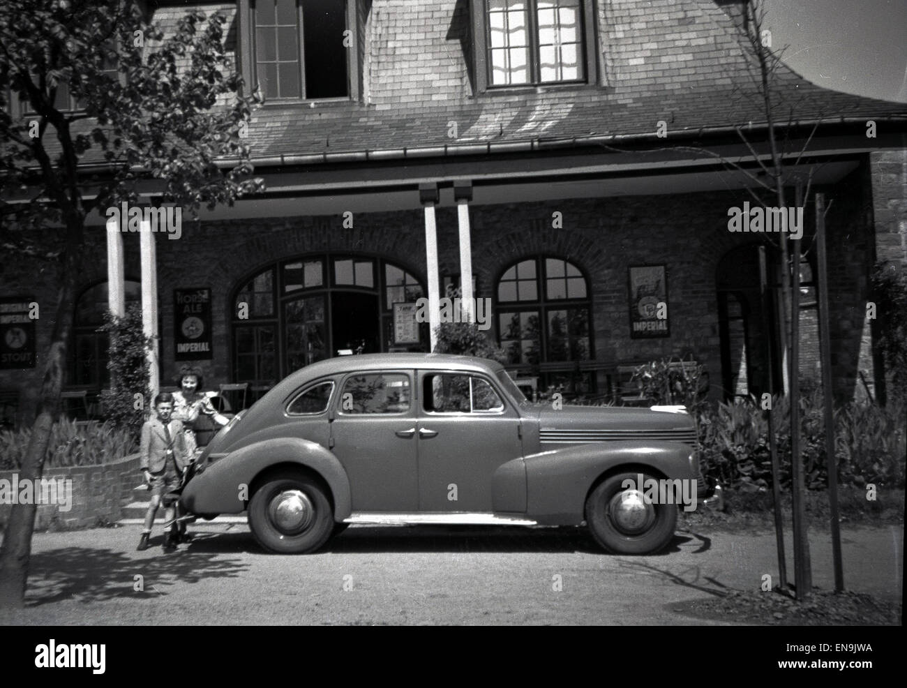 1930s, mother and young son stand by their car outside their home. - Stock Image