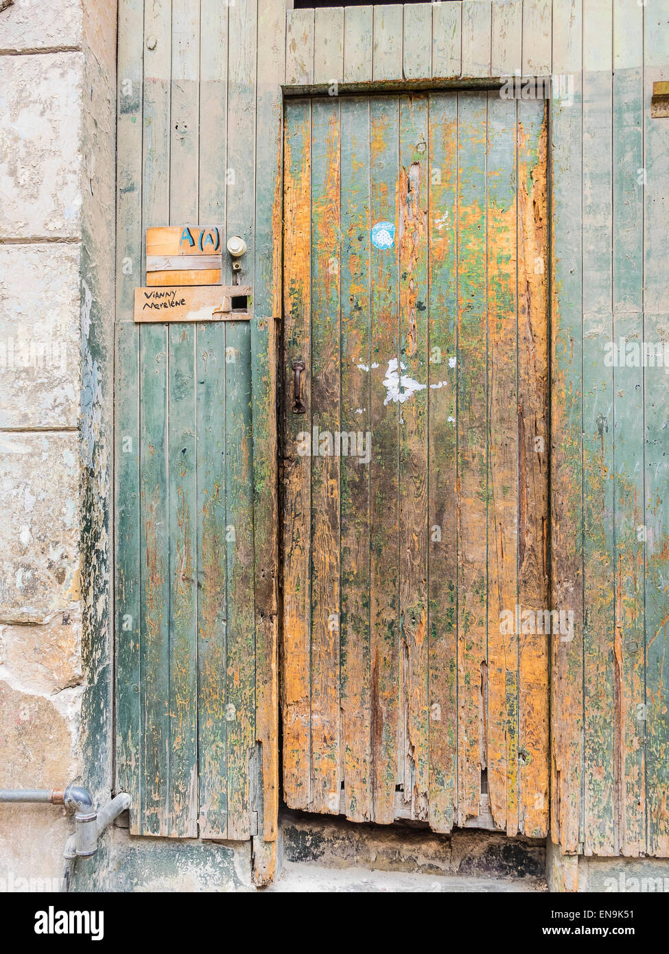 A beat-up wooden front door of a house in Havana Vieja, Cuba