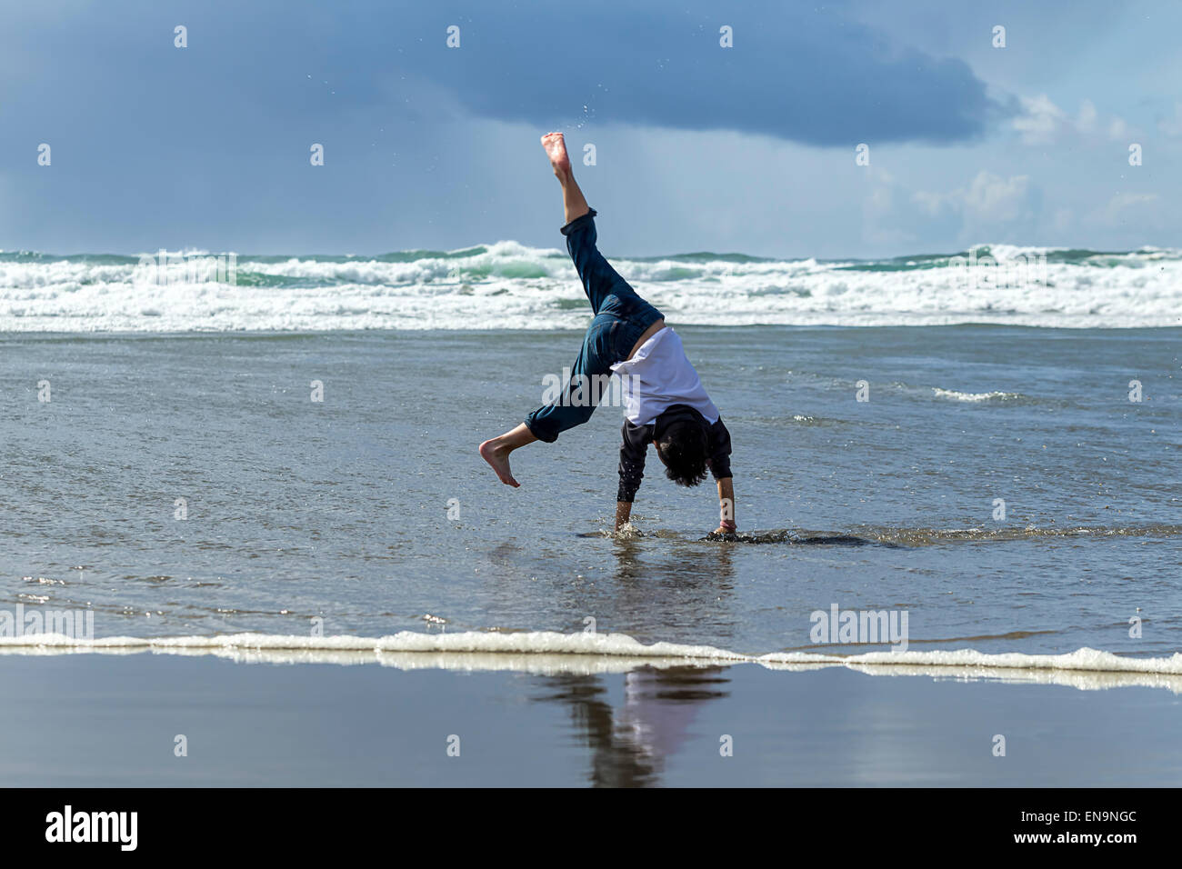 Boy does cartwheel on the beach. - Stock Image