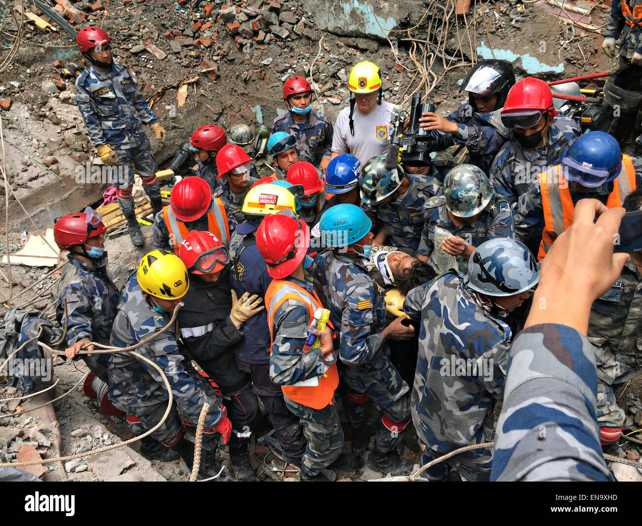 A USAID search and rescue team member from the Fairfax County Fire Department pulls a 15-year-old earthquake victim - Stock Image