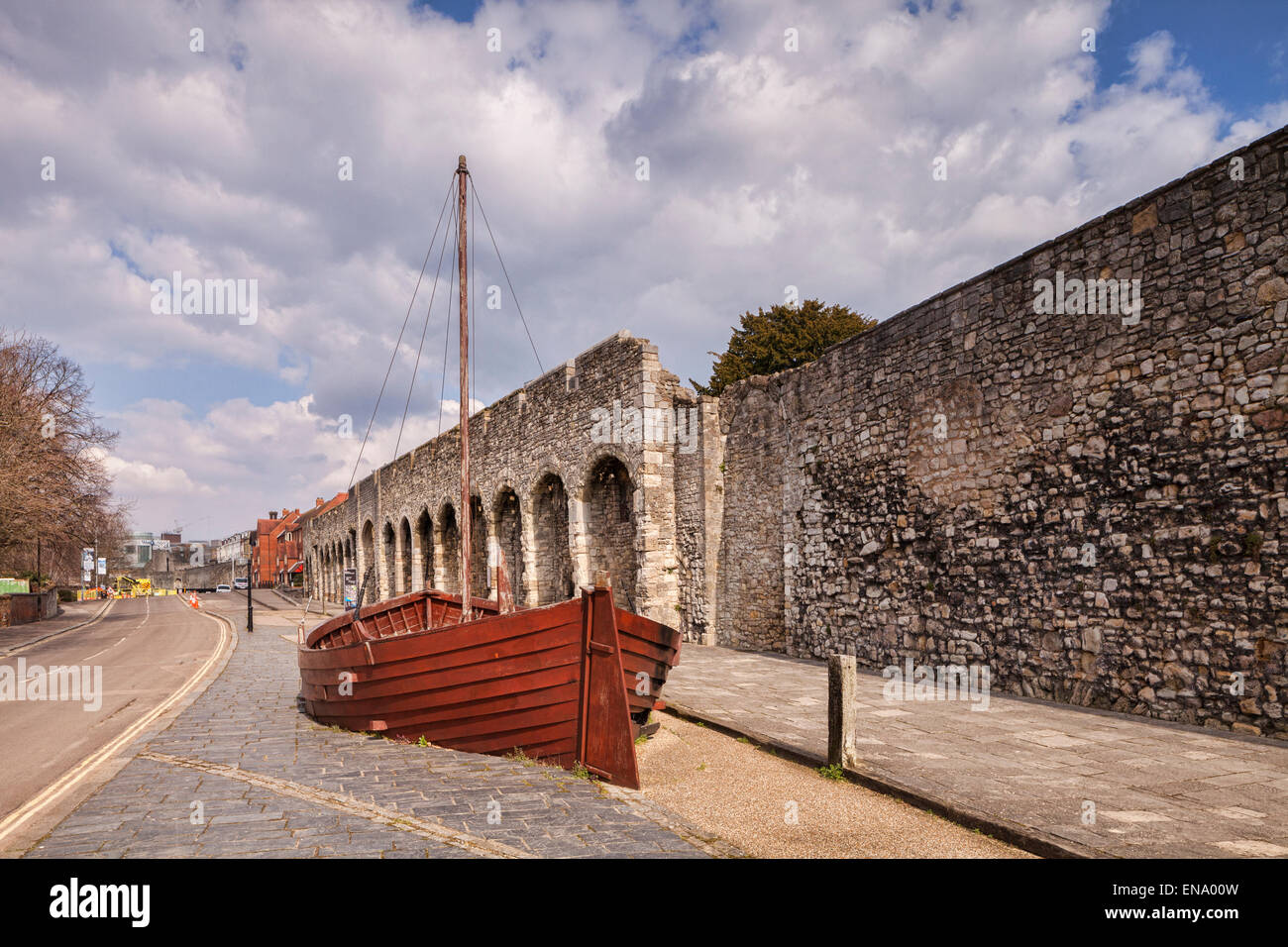 A section of the old city walls of Southampton. A boat has been placed to show where the sea was in medieval times. - Stock Image