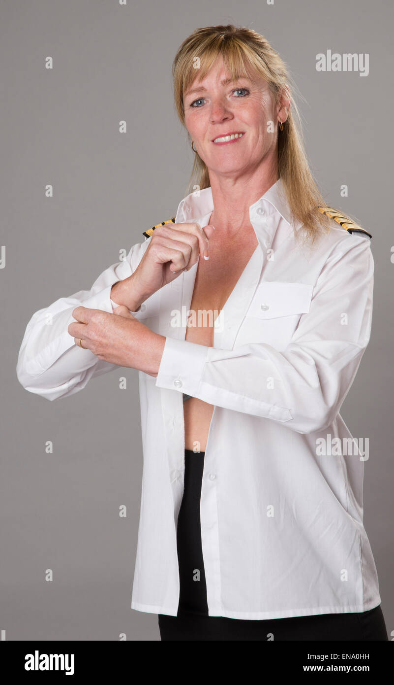 Woman airline officer buttoning white uniform shirt cuff before reporting for duty - Stock Image