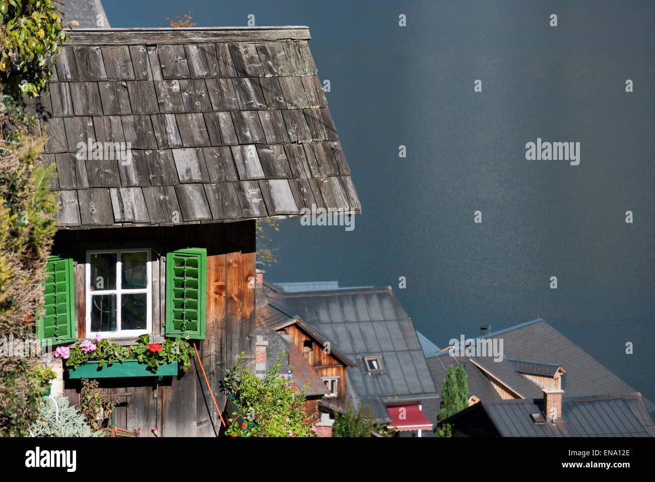 Holzhütte mit Fenster, Blumen und grünen Fensterläden über Hallstatt, Salzkammergut, Austria - Stock Image