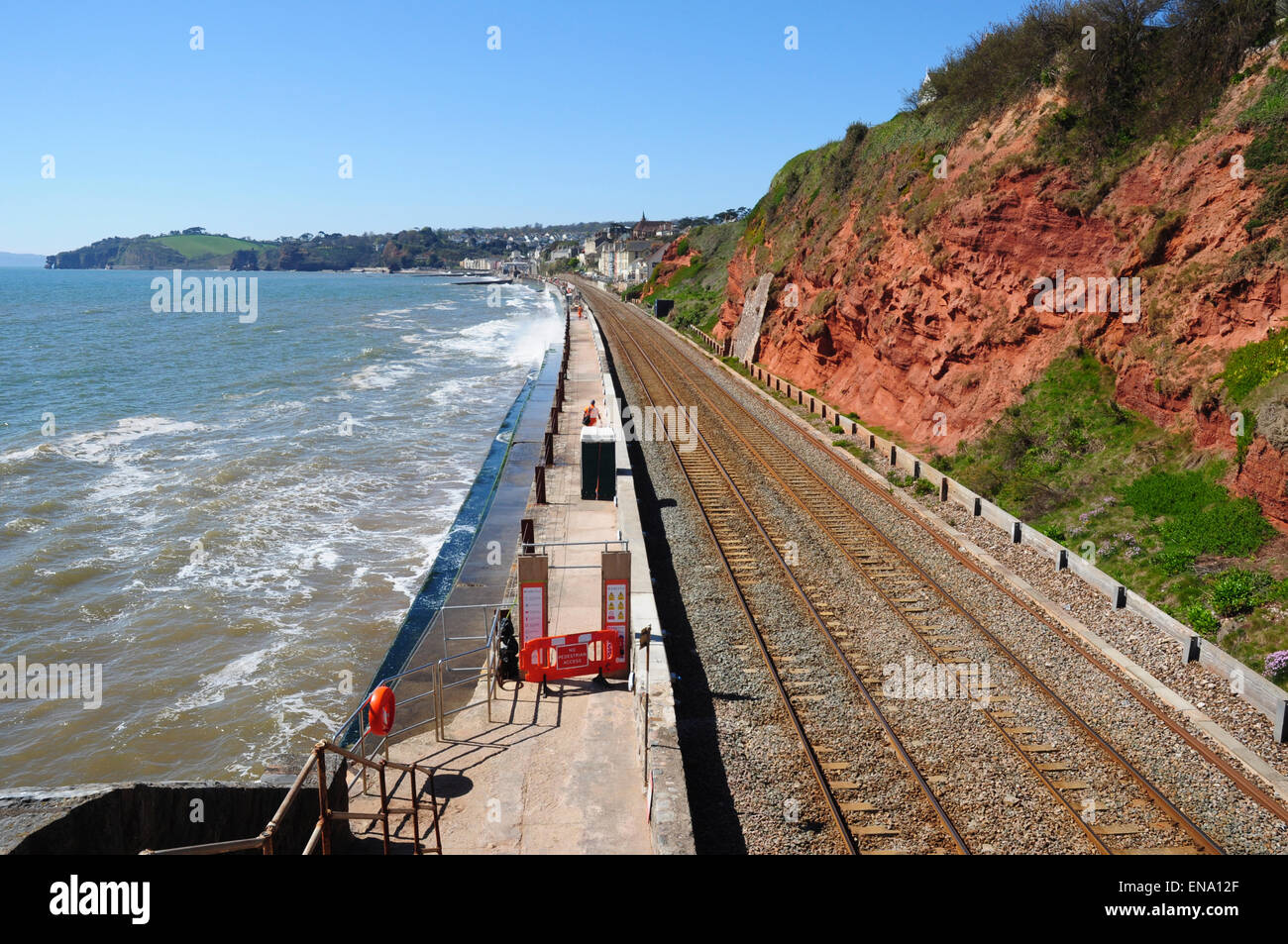Main railway line and red rock cliff face along the coast looking west to Dawlish, Devon, England, UK - Stock Image