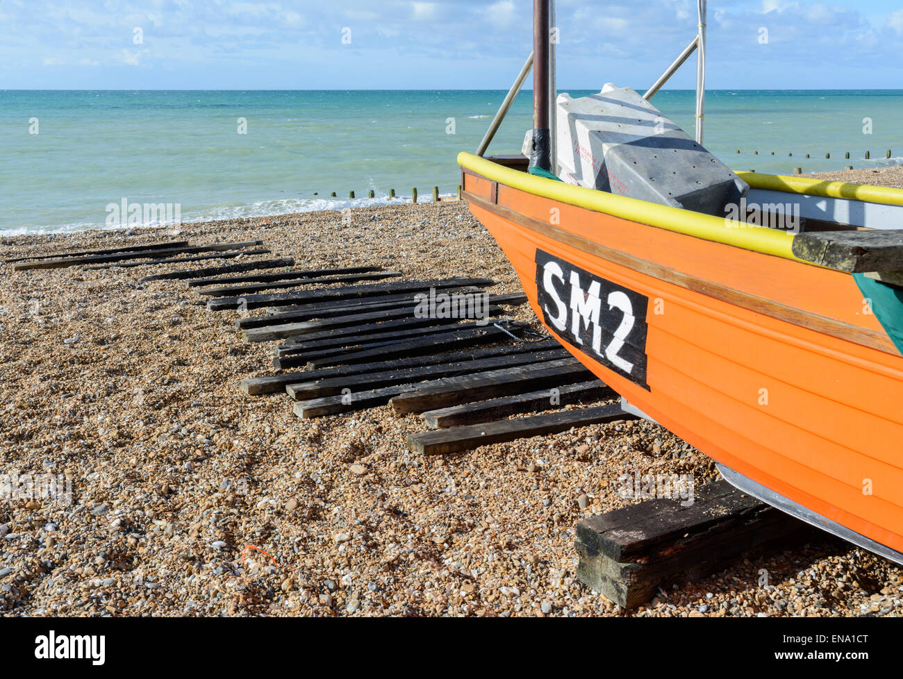 Small wooden orange fishing boat and launching rollers on a shingle beach. - Stock Image