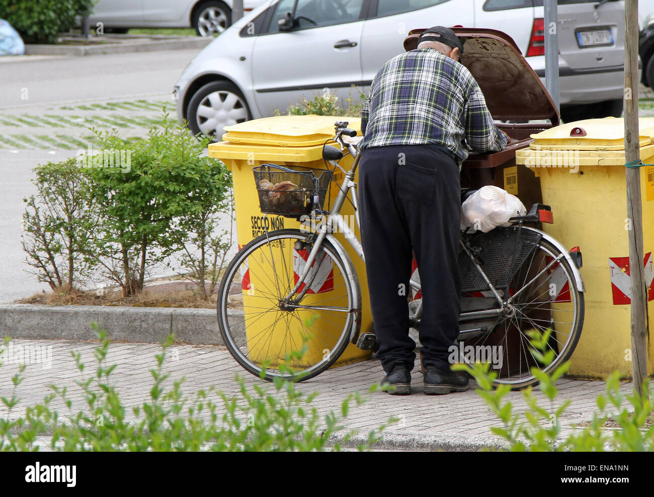 ITALY, Pordenone: An old man looking in the garbage for something to eat, while at Milano is started Expo 2015 - Stock Image