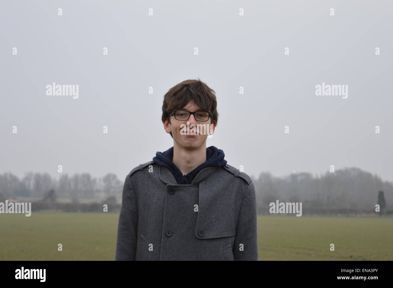 A skeptical model with a backdrop of a gray North Norfolk day - Stock Image