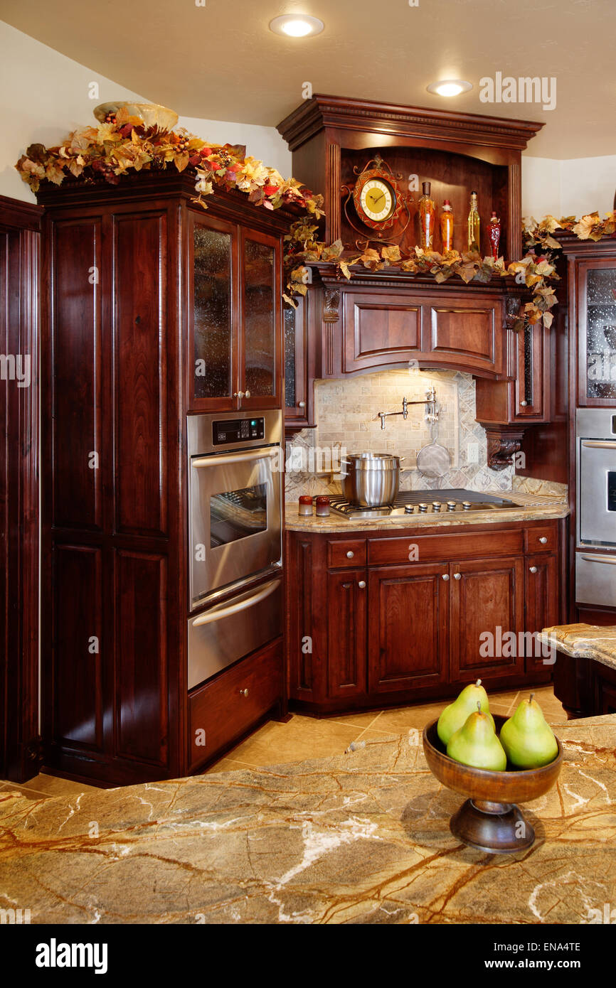 A modern kitchen featuring dark wood cabinets, stainless steel fixtures and granite counter tops. Stock Photo