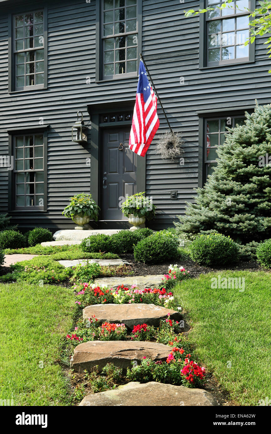 An image of the exterior and landscaping at a primitive colonial salt box style reproduction home. - Stock Image