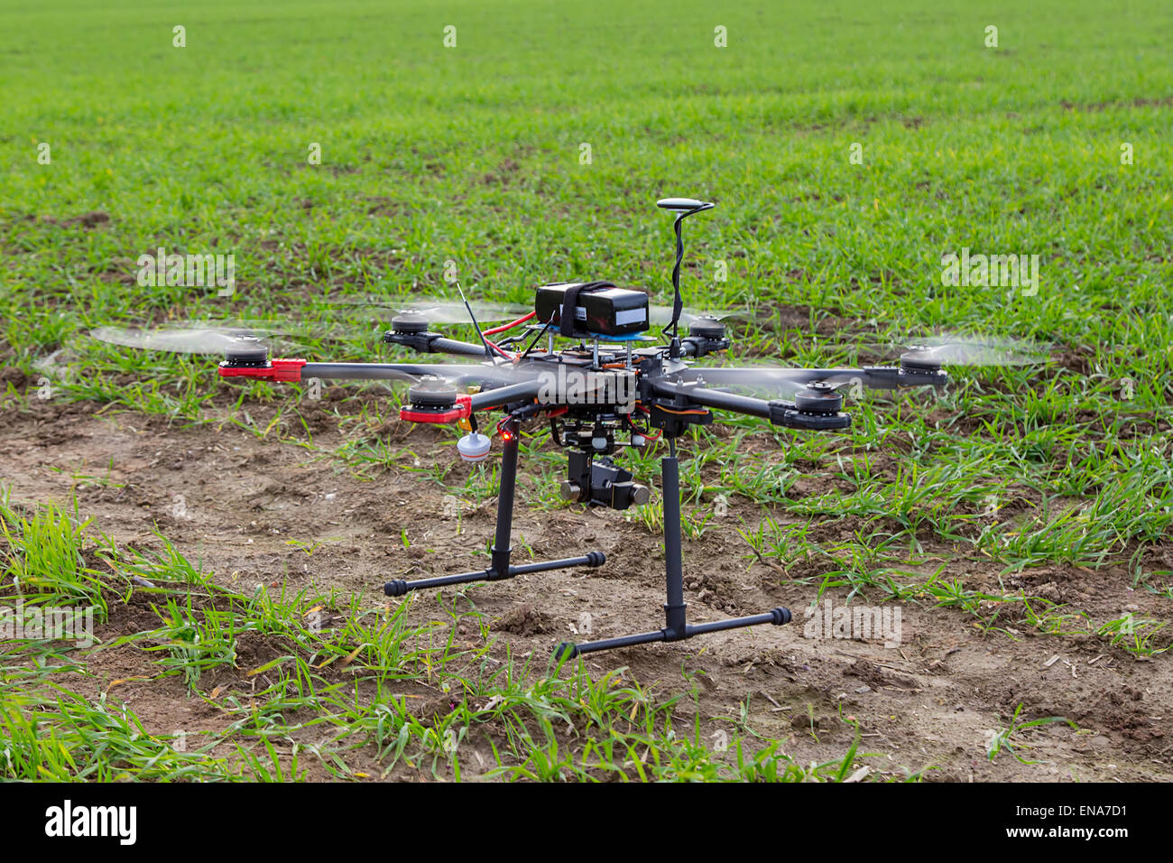 The small drone hexacopter flying over the field - Stock Image