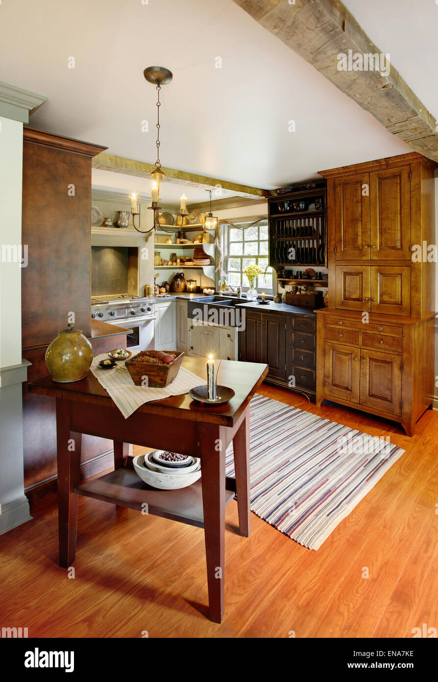 A modernized kitchen in a primitive colonial style reproduction home. - Stock Image