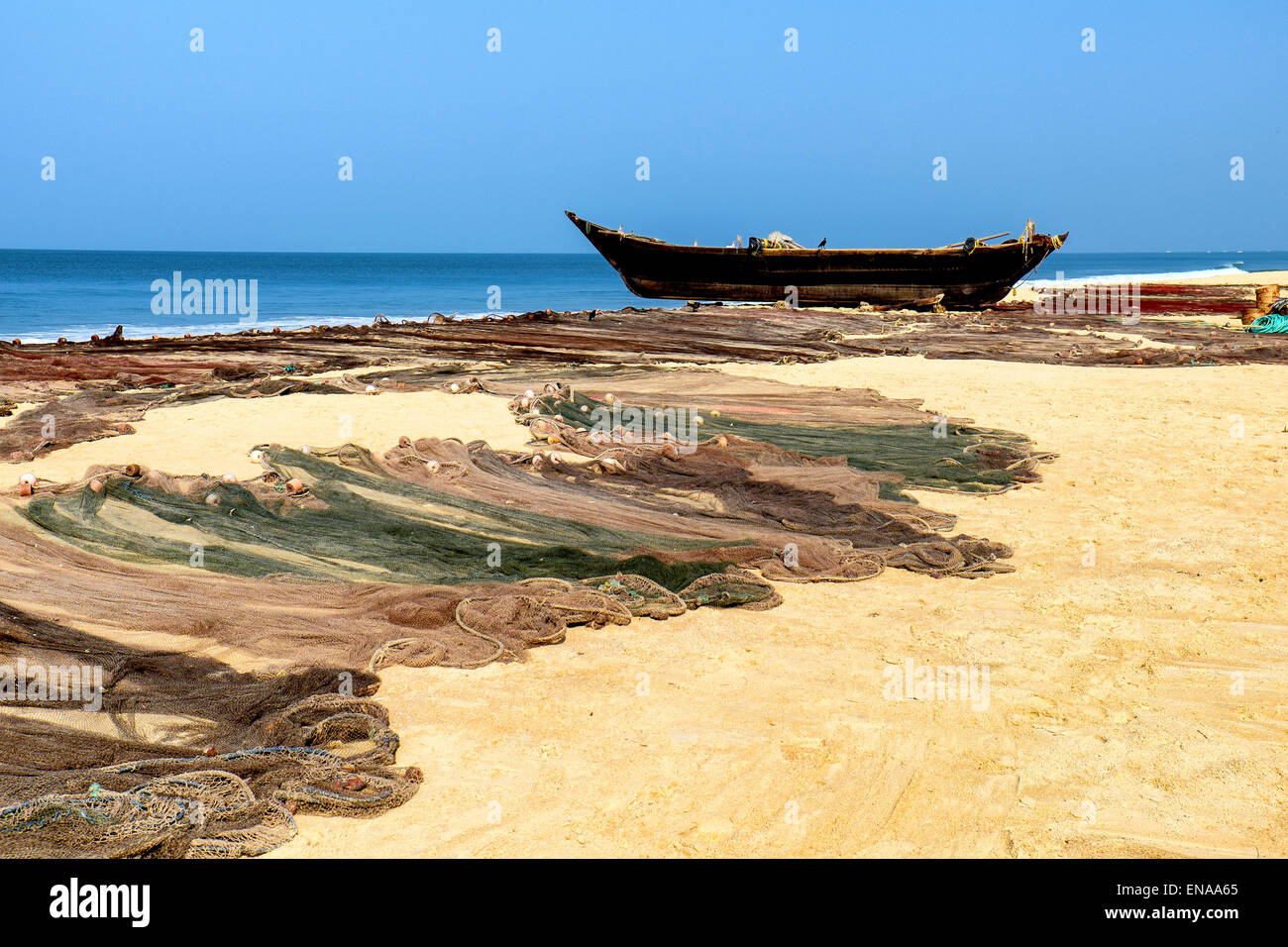 Goan Fishing boat with fishing nets in the foreground on Cavelossim, Salcette Goa - Stock Image